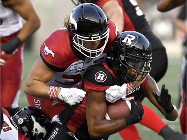 Ottawa Redblacks Loucheiz Purifoy (5) is tackled by Calgary Stampeders Ante Milanovic-Litre (34) during first half CFL action in Ottawa on Thursday, July 12, 2018.