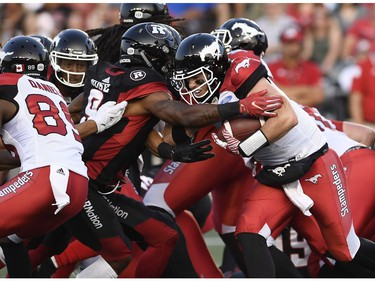 Calgary Stampeders quarterback Nick Arbuckle (9) tries to make his way past Ottawa Redblacks Jonathan Rose (9) during first half CFL action in Ottawa on Thursday, July 12, 2018.