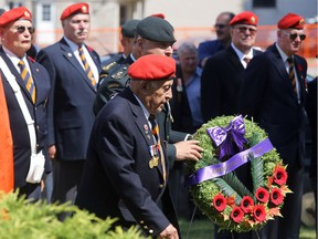 Second World War veteran Austin Fuller of the Tyendinaga Mohawk Territory walks with Lt.-Col. Chris Comeau, commanding officer of the Hastings and Prince Edward Regiment, during a service commemorating the 75th anniversary of the Allied invasion of Sicily Tuesday, July 10, 2018 in Belleville, Ont. Together they laid a wreath on behalf of the Mohawks of the Bay of Quinte band. Luke Hendry/Belleville Intelligencer/Postmedia Network