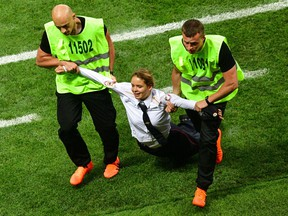 A pitch invader, a member of the Russian protest-art group Pussy Riot, is escorted by stewards during the Russia 2018 World Cup final football match between France and Croatia at the Luzhniki Stadium in Moscow on July 15, 2018. (Mladen Antonov/Getty Images)