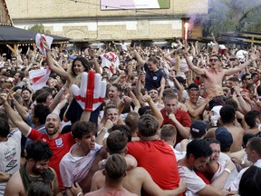 England soccer fans celebrate on the final whistle as they watch a live broadcast on a big screen of the quarterfinal match between England and Sweden at the 2018 soccer World Cup, in Flat Iron Square, south London, Saturday, July 7, 2018.