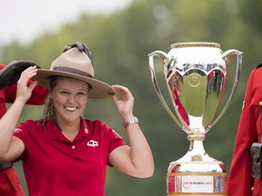 Brooke Henderson of Smiths Falls, ON tries on RCMP hat as she accepts the trophy after winning the CP Women's Open in Regina, Sunday, August 26, 2018.