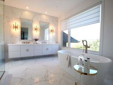 A Maxx Louie soaker tub beckons in the master ensuite, which is bathed in shades of white and gold for a calm and luxurious feel. It has the look of marble, but is done in a more affordable ceramic tile. Julie Oliver/Postmedia