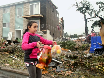 - Nine-year-old Emna Ben-Salem carries out some of the toys she could find in her bedroom of her family's home (rear), which will more than likely be demolished as half the roof and side on the triplex was ripped off in the tornado. The family car sits upended under a tree (at right). Demolition started in the Mont-Bleu area of Gatineau Tuesday following the tornado that ripped through the housing development Friday. People could be found gathering up what little they could find in the remains of their homes as crews worked to demolish unsafe buildings and clean up debris.  Julie Oliver/Postmedia