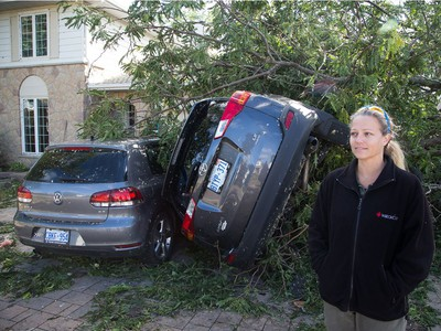 Renata Scorsone stands outside her home on Conover St on Saturday morning where her two vehicles were damaged as residents in Ottawa's west end deal with the aftermath of the twister that touched down on Friday afternoon.
