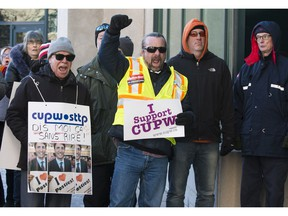 Allies of postal workers, including CUPW Local 580 president Ian Anderson (yellow vest), protest outside the Canada Post annual meeting in Ottawa. December 12, 2018.