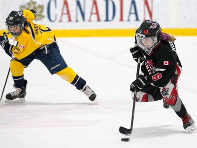 Jordan Mulvihill of the Nepean Wildcats in the Girls Atom AA division skates past Zoe Ordanis of the Whitby Wolves as the annual Bell Capital Cup hockey tournament for Peewee and Atom level players gets underway at the Bell Sensplex and various arenas across the city.