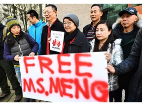 People hold a sign at a B.C. courthouse prior to the bail hearing for Meng Wanzhou, Huawei's chief financial officer on Monday. Meng was released on bail Tuesday.