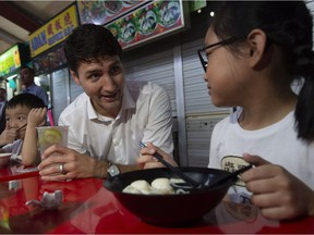 Prime Minister Justin Trudeau speaks with children as he visits the Adam road food centre in Singapore in November.  Trudeau has a family connection to Singapore, but he didn't tell the whole story.