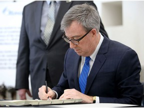 Mayor Jim Watson signs a Book of Condolences in memory of the victims of Friday's Westboro bus crash.