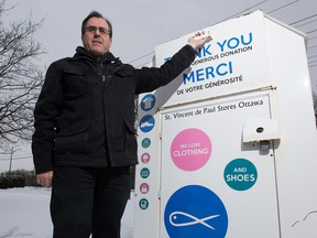 Richard Pommainville, executive director of the Saint Vincent de Paul Society, with one of their donation bins. Piommainville says it would be difficult to get into one of the boxes.