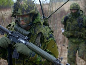 Canadian soldiers conduct dismounted patrols in a training area.