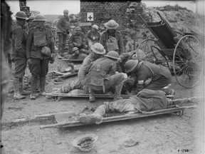 Dressing wounded Canadians during advance to Hill 70. August, 1917.