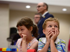 In this file photo, Social Development Minister Jean-Yves Duclos is shown in the background while a few younger Canadians focus on play. How should we interpret government announcements on child poverty reduction goals?