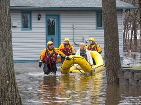 A woman is brought out of her home by Ottawa Fire as flood water rises in Constance Bay.