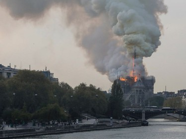 Smokes ascends as flames rise during a fire at the landmark Notre-Dame Cathedral in central Paris on April 15, 2019 afternoon, potentially involving renovation works being carried out at the site, the fire service said.