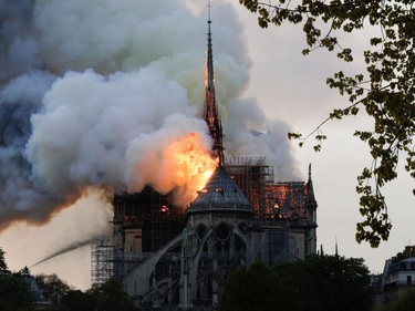 TOPSHOT - Flames and smoke are seen billowing from the roof at Notre-Dame Cathedral in Paris on April 15, 2019. - A fire broke out at the landmark Notre-Dame Cathedral in central Paris, potentially involving renovation works being carried out at the site, the fire service said.