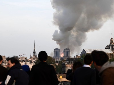 People watch the landmark Notre-Dame Cathedral burning in central Paris on April 15, 2019. - A huge fire swept through the roof of the famed Notre-Dame Cathedral in central Paris on April 15, 2019, sending flames and huge clouds of grey smoke billowing into the sky. The flames and smoke plumed from the spire and roof of the gothic cathedral, visited by millions of people a year. A spokesman for the cathedral told AFP that the wooden structure supporting the roof was being gutted by the blaze.