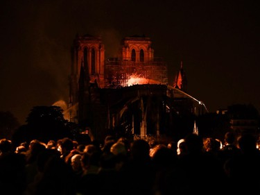 Bystanders look on as flames and smoke billow from the roof at Notre-Dame Cathedral in Paris on April 15, 2019. - A major fire broke out at the landmark Notre-Dame Cathedral in central Paris sending flames and huge clouds of grey smoke billowing into the sky, the fire service said. The flames and smoke plumed from the spire and roof of the gothic cathedral, visited by millions of people a year, where renovations are currently underway.