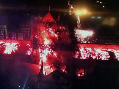 An image taken from a television screen shows an aerial view of the Notre-Dame Cathedral engulfed in flames on April 15, 2019, in the French capital Paris. - A huge fire swept through the roof of the famed Notre-Dame Cathedral in central Paris on April 15, 2019, sending flames and huge clouds of grey smoke billowing into the sky. The flames and smoke plumed from the spire and roof of the gothic cathedral, visited by millions of people a year. A spokesman for the cathedral told AFP that the wooden structure supporting the roof was being gutted by the blaze.