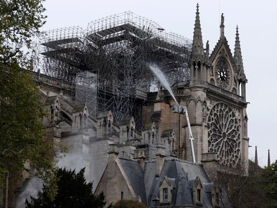 """TOPSHOT - Firefighters spray water as they work to extinguish a fire at Notre-Dame Cathedral in Paris early on April 16, 2019. - A huge fire that devastated Notre-Dame Cathedral is """"under control"""", the Paris fire brigade said early on April 16 after firefighters spent hours battling the flames."""