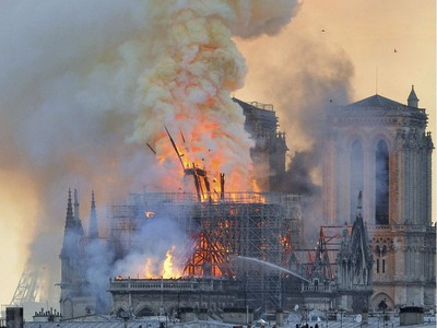 "In this image made available on Tuesday April 16, 2019 flames and smoke rise from the blaze after the spire toppled over on Notre Dame cathedral in Paris, Monday, April 15, 2019. An inferno that raged through Notre Dame Cathedral for more than 12 hours destroyed its spire and its roof but spared its twin medieval bell towers, and a frantic rescue effort saved the monument's ""most precious treasures,"" including the Crown of Thorns purportedly worn by Jesus, officials said Tuesday."