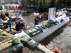Residents and volunteers put sand bags along the  Britannia berm in Ottawa Monday. The wall on Jamieson Street is the weakest part of the berm which if destroyed will flood the entire neighbourhood of Britannia.