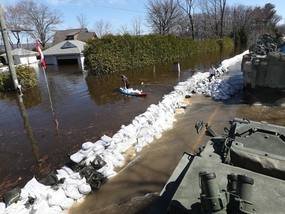 Media traveling with the Canadian Armed Forces during a flooding tour of Constance Bay in Ottawa Tuesday April 30, 2019. Members got a opportunity to watch the Canadian Armed Forces flood relief operations Tuesday. A woman carries sandbags in a canoe to her home.