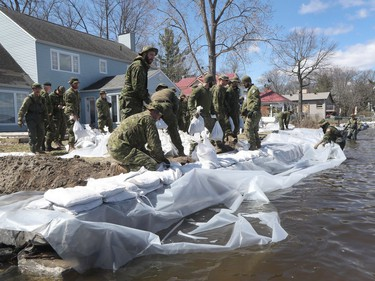 Armed forces personnel place sandbags to prevent flooding in Constance Bay.
