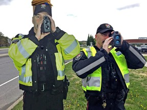 Life-size cutout of 'Constable Scarecrow' on left, with traffic officer Const. Luc Mongeon on the right.