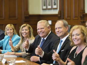 Ontario Premier Doug Ford sits with members of his cabinet after a cabinet shuffle at Queens Park on June 20, 2019.