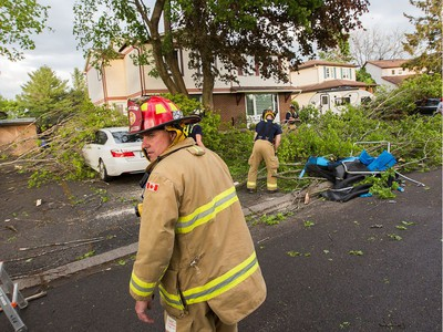 Firefighters at work clearing damaged branches on Singleton Way as a reported tornado touched down in the Orléans suburb of Ottawa on Sunday evening. Wayne Cuddington / Postmedia