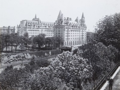 Chateau Laurier Hotel shown in photograph taken from across the Rideau Canal at the back of the Parliament Buildings shortly after hotel expansion in 1929-30. Note railway line running along east side of canal beside and behind the hotel.