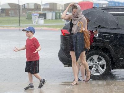 Jacqueline Bell and her son, Frank, 8, run for cover after arriving at the Canadian War Museum during the severe weather as the second day of RBC Bluesfest gets going on Friday evening.