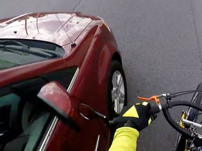 An Ottawa cyclist posted a video to YouTube on Friday, in which a minivan appears to narrowly hit the bike's handlebar mirror after an altercation on Cyrville Rd.