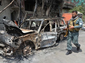 A member of Afghan security forces walk at the site of an attack in Kabul on July 29, 2019, a day after a deadly assault targeting a political campaign office.