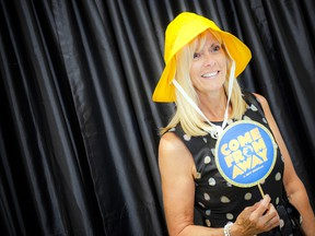 Lynn Laberge poses with props in a photo booth.