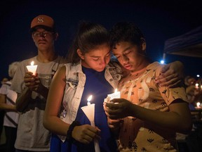People pray during a candlelight vigil at the Immanuel Church for victims of a shooting that killed 22 people at a WalMart in El Paso. President Donald Trump has said little about gun control in the days since.