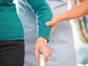 A stock file photo of a senior woman receiving assistance from a health care worker with a walking frame.