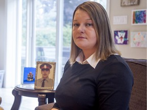 Tricia Kirkwood with her father's photo and police badge. Ottawa police constable David Kirkwood was shot and killed in the line of duty on July 11, 1977.
