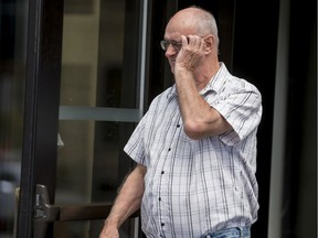 Former Scout leader Donald Joseph Sullivan tires to cover his face as he leaves the Ottawa courthouse in August 2019.