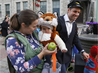 """Allison Ensom, left, and Juniper, 9 months, get an apple at the """"Trick or Treat with the Mayor"""" Halloween event at City Hall on Saturday."""