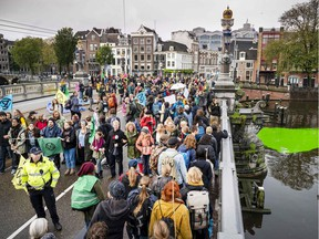 """Activists from the """"Extinction Rebellion"""" climate change action group block the Blauwbrug bridge on October 12, 219, in Amsterdam."""