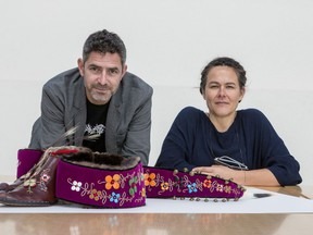 """Greg A. Hill, curator, and Rachelle Dickenson, curator, with work by artist Barry Ace entitled """"Nigik Makisinian-Otter Moccasins"""", 2014, National Gallery of Canada."""