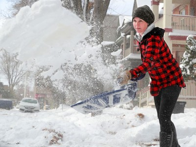 Dee MacLennan puts her back into it, clearing her driveway on Regent Street following the wallop of snow overnight that left Ottawans shovelling and digging out their cars Tuesday morning.