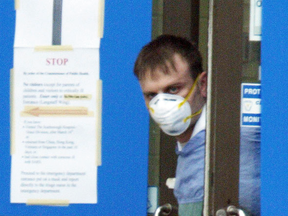 A staff member at York Central hospital in Richmond Hill, Ont., glances out the doors of the closed facility after fears the 2003 SARS outbreak was spreading further. At its peak, the outbreak caused people to avoid human contact, one epidemiology professor says.