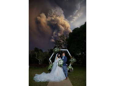 A couple attends their wedding ceremony as Taal Volcano sends out a column of ash in the background in Alfonso, Cavite, Philippines, January 12, 2020, in this image obtained from social media.