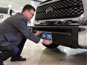 MPP Bill Walker holds up a new Ontario commercial vehicle licence plate on the front bumper of a truck. All licence plates issued in Ontario will be modelled off this new plate design starting Feb. 1, 2020, according to a news release from Walker's office.