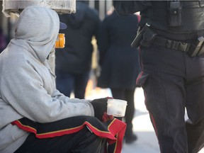 A homeless man begs for money with a plastic cup on Elgin Street.