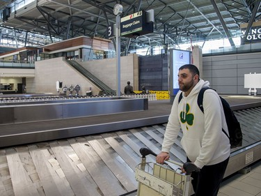 Steve Marcus, a professional basketball coach working with a team in St John's NFLD, waits to pick up his bags before renting a car and heading home to Boston, Mass, as COVID-19 has shut down most airline travel and all sporting activities around the world.